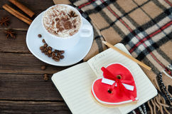 Cozy rest. Mug latte, notepad with pencil, gingerbread-heart, plaid plaid and coffee beans. Stock Images