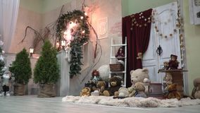 A cozy room with Christmas decorations, garlands, toys, coniferous trees. Beautiful light room with plush toys and Christmas decorations stock footage