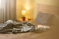 Comfortable bed with soft pillow in room interior stock photos