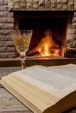 Cozy scene before fireplace with glass of wine and book. Glass of wine and book near cozy fireplace in country house, winter vacation royalty free stock photography
