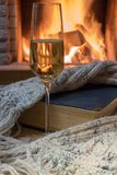 Cozy scene before fireplace with a glass of wine, a book, wool scarf. Glass of wine and warm wool scarf , a book , near cozy fireplace, in country house, winter royalty free stock photography