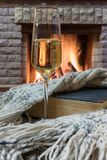 Cozy scene before fireplace with glass of wine, book and wool warm scarf. Glass of wine, book and warm wool scarf near cozy fireplace in country house, winter royalty free stock photos