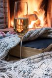 Cozy scene before fireplace with glass of wine, book and wool warm scarf. Glass of wine, book and warm wool scarf near cozy fireplace in country house, winter stock images