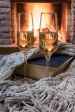 Cozy scene before fireplace with glass of wine, book and wool warm scarf. Glass of wine, book and warm wool scarf near cozy fireplace in country house, winter royalty free stock photography