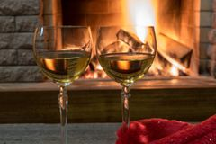 Cozy scene before fireplace with two glasses of wine. Two glasses of wine near cozy fireplace in country house, winter vacation royalty free stock photography