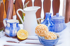 Cozy Scene with Vintage Blue Cups, Vases, Decanters in the Snow stock photo
