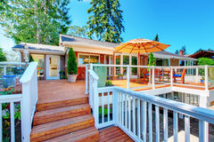 Cozy screened walkout deck with patio area and white railings staircase. Stock Image