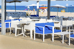 Cozy sea  restaurant with white chairs and blue pillows Stock Photography