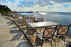 Sea Restaurant with Wooden Tables and Chairs on the Sea Shore with Sea View. Cozy Sea Restaurant with Wooden Tables and Chairs with Sea View royalty free stock image