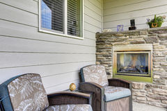 Cozy sitting area with two comfortable armchairs and fireplace with natural stone decor. Stock Photo