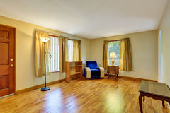 Cozy sitting room with hardwood floor and blue armchair in the corner. Royalty Free Stock Photography