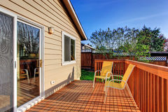 Cozy small backyard with wooden walkout deck Stock Photography