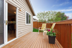 Cozy small backyard with wooden walkout deck Royalty Free Stock Photo