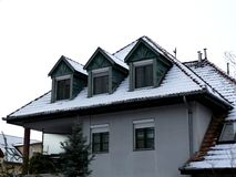 Snowy rustic roof with dormers on winter day with pine tree stock photo