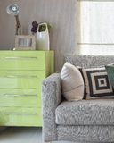 Cozy sofa with geometric pattern pillows and green sideboard in Stock Photos