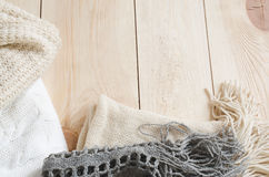 Cozy and soft winter background. Warm knitted clothes on a wooden background. Stock Photography