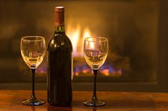 Cozy space. Bottle of wine with two empty glasses in front of a warm fire royalty free stock image