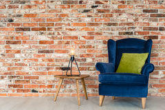 Cozy spot in the room. Cozy spot with armchair in the room with brick wall royalty free stock photography