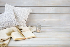 Cozy still life with lantern, pillows, book and plaid Royalty Free Stock Photography