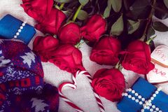 Cozy still life for St. Valentine`s Day with roses and gifts. Cozy still life for St. Valentine`s Day of red roses, blue gifts and gingerbread cookie royalty free stock images