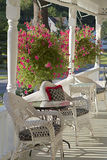 Cozy Summer Niche. A country porch with white, wicker chairs and cushions.  White railings hung with sprawling baskets of hanging pink flowers, lit by lazy Royalty Free Stock Image