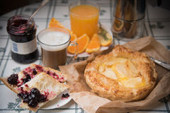 A cozy sweet breakfast in bright colors. Apple pie with cherry jam and cups of hot coffee and fresh orange juice. Stock Photography