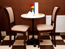 Cozy table and two chairs in the cafe. Royalty Free Stock Image