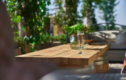 Cozy terrace with sofas for rest, Glass with champagne on a wooden table. Sunny day Stock Photo