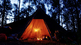 Cozy tipi with oil lamps and camp fire in a dark forest Royalty Free Stock Photos