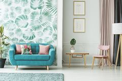 Cozy turquoise couch. Wooden table and chair in a white and green living room interior with plants and leaf patterns Royalty Free Stock Images