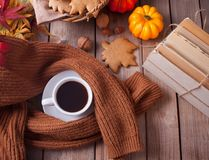Cup of coffee, autumn leaves, pumpkin, cookies, books and sweater on the wooden table. Autumn harvest. Autumn concept. Top view