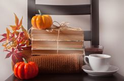 Cup of coffee, autumn leaves, pumpkin, books and sweater on the wooden chair. Autumn concept