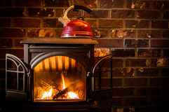 Cozy, warm fire heating a kettle against a brick hearth. Inside a cabin stock photography