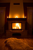 Cozy warm fireplace. A view of a comfortable, warm fireplace with a blazing fire in a sitting or living room Royalty Free Stock Photography