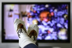 Free Cozy Warm Winter Christmas Socks With A Reindeer. Person Watching A Christmas Movie On The Television Stock Photos - 165557733
