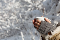 Cozy warmth. Women's hands in gray fingerless knitted mittens and coat with white fur holding white cup of tea at the background of snowy forest. Close up Stock Image