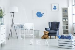 Cozy white and blue nursery. With suede armchair and whale poster over a wooden crib royalty free stock photography