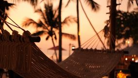 Cozy white hammock on the beach against a background of the swimming pool, ocean and sunset. Cozy white hammock on the beach against a background of the stock video
