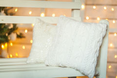 Cozy white pillows. On the bench, christmas lights on background Royalty Free Stock Photography