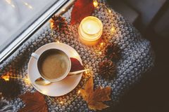 Cozy winter or autumn morning at home. Hot coffee with gold metallic spoon, warm blanket, garland and candle lights royalty free stock photos