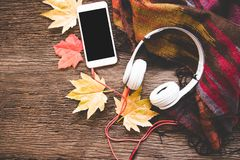 Cozy winter background, cup of hot coffee with marshmallow and headphone music, smart phone,warm knitted sweater, vintage tone. Stock Photo