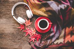 Cozy winter background, cup of hot coffee with marshmallow and headphone music, warm knitted sweater, vintage tone. Lifestyle and music concept Royalty Free Stock Images
