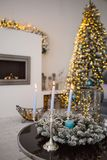 Cozy winter christmas interior with candles, fireplace and Christmas tree Royalty Free Stock Photo
