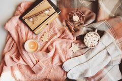 Cozy winter or Christmas table with seasonal fashion clothes, hot cocoa and candles. Hygge concept stock photography