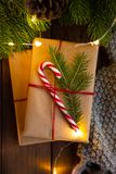 Close-up. Cozy winter christmas photo. Gifts wrapped with craft paper, decorated with candy caneon a rustic dark wooden stock photo