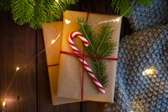 Close-up. Cozy winter christmas photo. Gifts wrapped with craft paper, decorated with candy caneon a rustic dark wooden royalty free stock images