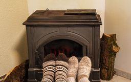Cozy winter concept: two pairs of foots in wool socks in front of the old iron stove royalty free stock images