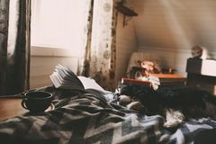 Cozy winter day at home with cup of hot tea, book and sleeping do. G. Spending weekend in bed, seasonal holidays and hygge concept royalty free stock image