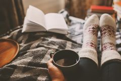 Cozy winter day at home with cup of hot tea, book and warm socks. Spending weekend in bed, seasonal holidays and hygge concept royalty free stock image
