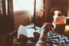 Cozy winter day at home with cup of hot tea, book and warm socks stock photos